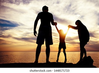 Happy Family Silhouette on the Sunset Background