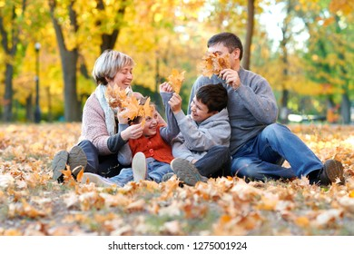 Happy family sit in autumn city park on fallen leaves. Children and parents smiling, playing and having fun. Bright yellow trees.