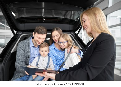 Happy family sitting in car trunk, buying new automobile in car dealership. Beautiful woman, car dealer holding black folder with document. Man signing contract, purchasing vehicle.