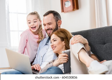 Happy family sitting embracing on sofa and using laptop