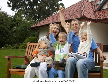 Happy family sitting in front of the house