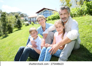 Happy family sitting in home private garden