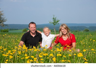 Happy family sitting in a meadow full of dandelions in spring