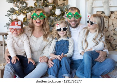 Happy family sitting near the Christmas tree in funny glasses.