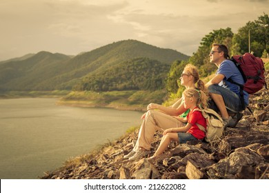 Happy family sitting near the lake at the day time. Concept of friendly family.