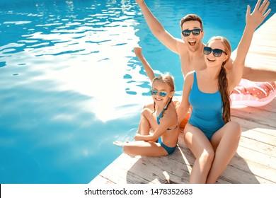 Happy family sitting near swimming pool