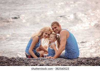 happy family sitting on the beach at sunset.