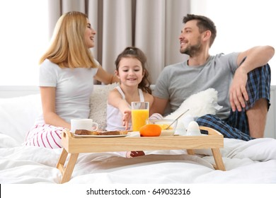 Happy family sitting on bed with breakfast