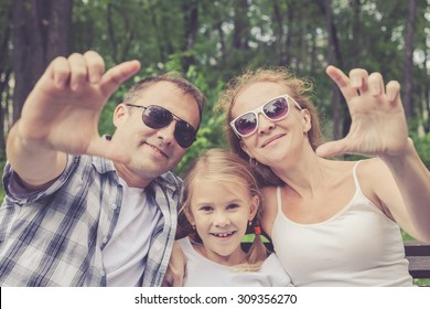 Happy family sitting on the bench in park at the day time