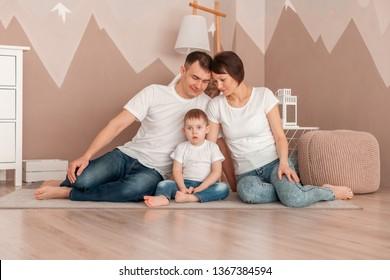Happy family sitting on the carpet in children's room