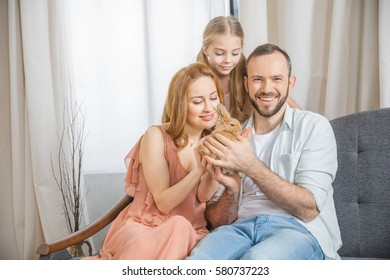 Happy family sitting on couch and playing with cute little rabbit