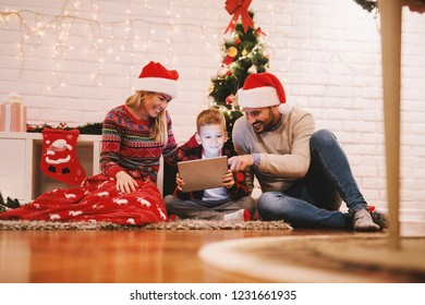 Happy family sitting on the floor in front of Christmas tree and watching videos on tablet. In background Christmas decorations.