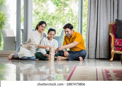 Happy Family sitting On floor Playing With The Wooden Blocks At Home