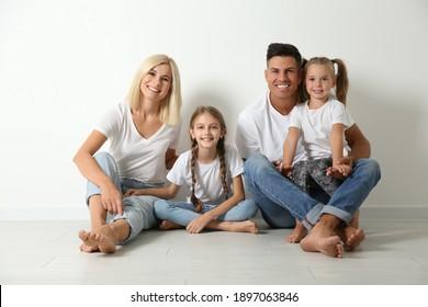 Happy family sitting on floor near white wall