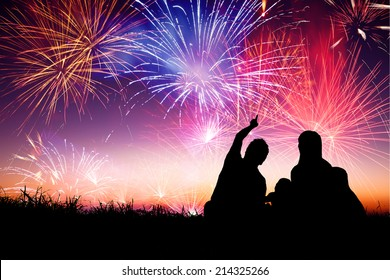 happy family sitting on floor and watching the fireworks