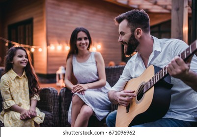 Happy family is sitting on house's terrace and smiling. Dad is playing guitar.