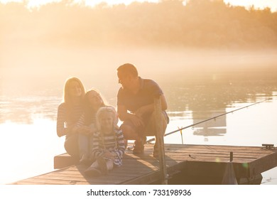 happy family sitting on the pier of the Dnieper River on the Sunset