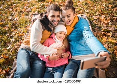 Happy family sitting on plaid in autumn park and taking selfie
