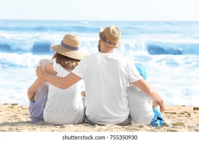 Happy family sitting on sea beach at resort