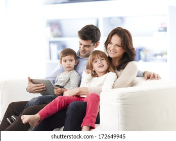 Happy family sitting on sofa in living room.