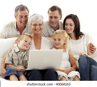 Happy family sitting on sofa using a laptop in living-room