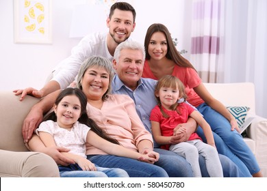 Happy family sitting on sofa in the room
