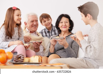 Happy family sitting on a sofa and having a dessert