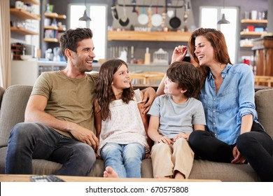 Happy Family Sitting On Sofa In Lounge Talking Together