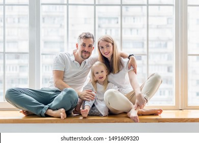 Happy family sitting on windowsill together. Family smiling while sitting in front of window