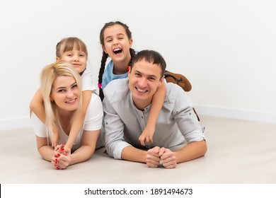 Happy family sitting on wooden floor. Father, mother and child having fun together. Moving house day, new home concept
