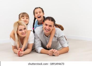 Fröhliche Familie, die auf Holzfußboden sitzt. Vater, Mutter und Kind, die zusammen Spaß haben. Wandertag, neues Wohnkonzept