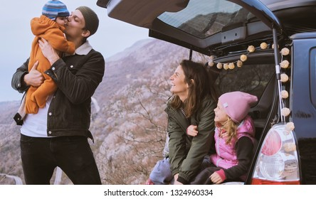 Happy Family  sitting in the open trunk of a black car with kids  against the backdrop of autumn mountains