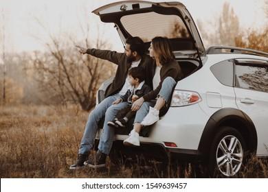 Fröhliche Familie sitzt am offenen Kofferraum von Heckenwagen und zeigt den Finger nach draußen. Konzept der Straßenfahrt.