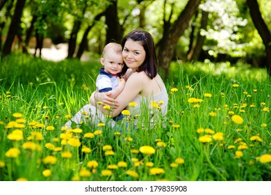 happy family sitting outside in a field of dandelion flowers