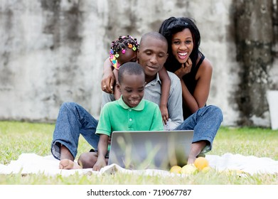 happy family sitting at the park and looking together on a laptop