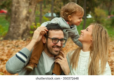 Happy family sitting in the park on autumn leaves