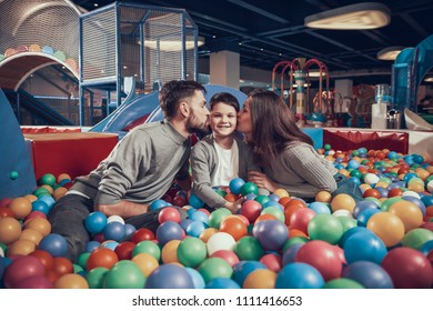 Happy family sitting in pool with balls. Parents kissing kid. Family rest, leisure. Spending holiday together. Entertainment center, mall, amusement park.