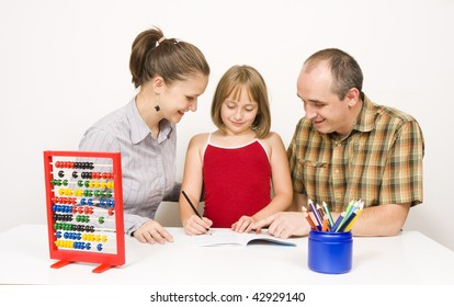 A happy family sitting together. the parents are helping their little daughter with the homework against white wall - some educational tools and objects on the table.