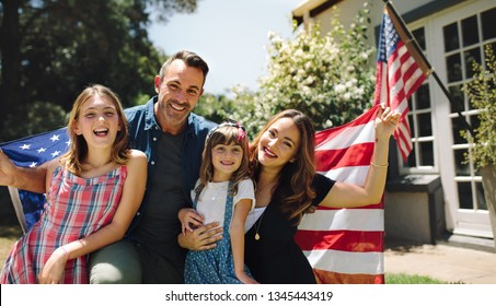 Happy family sitting together in their backyard holding the american flag behind them. Smiling couple with their kids celebrating american independence day holding american flag.