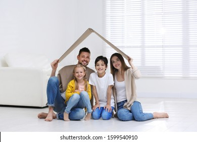 Happy family sitting under cardboard roof at home. Insurance concept