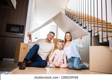 happy family sitting under paper roof and smiling in new home