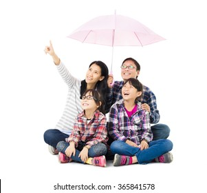 happy family sitting under an umbrella