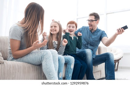 happy family sitting watching TV in their home