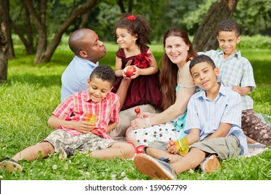 Happy family of six sits on rag matting and eats fruits and berries in summer park