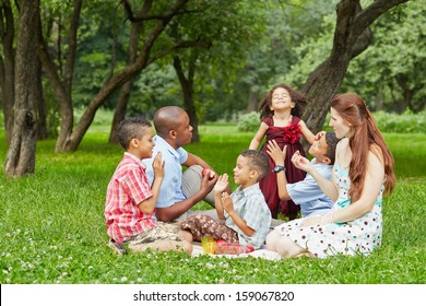 Happy family of six takes rest at picnic in summer park