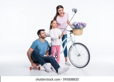 happy family with skateboard and bicycle making selfie isolated on white