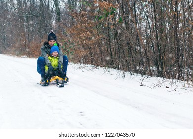 Happy family with sled in winter having fun together. Child sledding.Happy mother and her son enjoying sleigh ride. Family driving sled under winter snow. Christmas vacation. Winter holidays