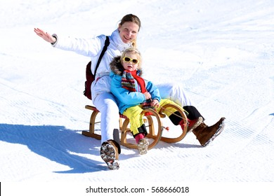 Happy family sledding from snowy mountain. Young mother and her little toddler daughter enjoying a ride on wooden sledge in a beautiful winter park