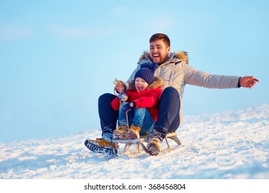 happy family sliding downhill on winter snow