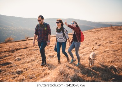 Happy family with small brown dog hiking together on a mountain